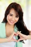 Femme de forme physique de beauté avec le signe de coeur Photo stock