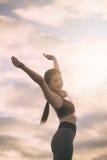 Femme de forme physique de silhouette s'exerçant au temps de coucher du soleil image stock