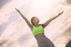 Femme de forme physique de silhouette s'exerçant au temps de coucher du soleil photographie stock libre de droits