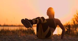 Femme de forme physique faisant des craquements ? la plage La femme de forme physique faisant des craquements exercent la s?ance  clips vidéos
