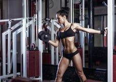 Femme de forme physique faisant des exercices avec l'haltère dans le gymnase Photos stock