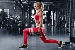Femme de forme physique faisant des exercices de mouvements brusques pour la séance d'entraînement de muscle de jambe dans le gym photos stock