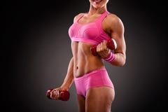 Femme de forme physique faisant la séance d'entraînement avec des haltères Photo stock