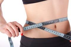 Femme de forme physique mesurant sa taille Photo libre de droits