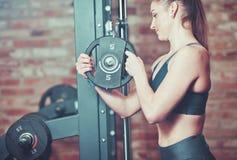 Femme de forme physique mettant le disque de poids au barbell contre le mur de briques dans le gymnase photo stock