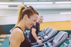 Femme de forme physique riant avec l'ami dans le tapis roulant Image stock