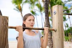 Femme de forme physique s'exerçant sur la barre de traction Images libres de droits