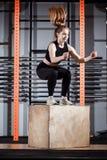 Femme de forme physique sautant sur la formation de boîte au gymnase, exercice convenable de croix photo libre de droits
