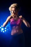 Femme de forme physique se tenant contre des lumières de couleur Photos libres de droits