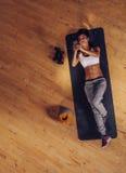 Femme de forme physique se trouvant sur le tapis utilisant le téléphone portable Image libre de droits