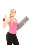 Femme de forme physique tenant un tapis de exercice et renonçant à un pouce Images stock