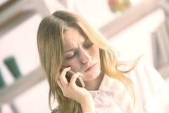 Femme de froncement de sourcils au téléphone image stock