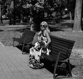 Femme de gamme de gris tenant son chien Photos libres de droits