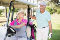 Femme de golfeur regardant l'homme tout en se reposant dans le boguet de golf Photo stock