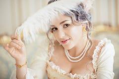 Femme de Greyhead dans la robe blanche avec la peau pâle sur le fond rococo Une femme de vampire avec une belle coiffure avec une photos stock