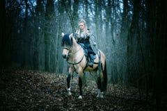 Femme de guerrier sur un cheval dans les bois Scandinave Viking photo stock