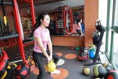Femme de gymnase dans le gymnase établissant utilisant des kettlebells d'intérieur Beau, presse photos stock