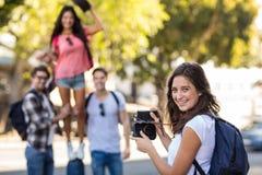 Femme de hanche prenant la photo de ses amis Photographie stock libre de droits