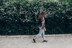 Femme de hippie dans des lunettes de soleil marchant sur le fond des Bu de floraison Image stock