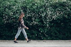 Femme de hippie dans des lunettes de soleil marchant sur le fond des Bu de floraison Photographie stock
