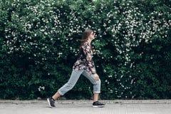 Femme de hippie dans des lunettes de soleil marchant sur le fond des Bu de floraison Photographie stock libre de droits