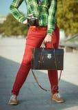 Femme de hippie dans le pantalon rouge et la chemise verte avec la vieille valise Images stock