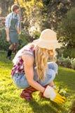 Femme de jardinier plantant une fleur avec son ami derrière Photos libres de droits