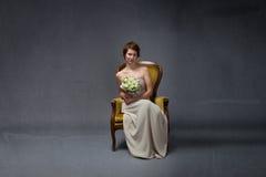 Femme de jeune mariée s'asseyant sur le sofa jaune photographie stock