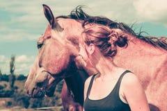 Femme de jockey prenant soin de cheval Images stock