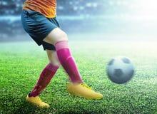 Femme de joueur de football dans le débardeur orange donnant un coup de pied la boule photographie stock libre de droits