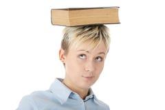 Femme de l'adolescence d'étudiant avec le livre sur la tête Photographie stock