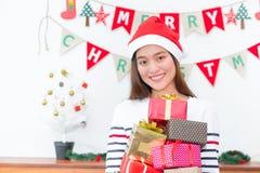 Femme de l'Asie en partie de Noël tenant le groupe de la boîte actuelle avec le smili Photographie stock