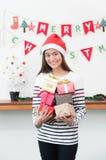 Femme de l'Asie en partie de Noël tenant le groupe de la boîte actuelle avec le smili Images libres de droits