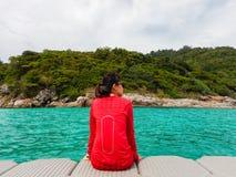 femme de l'Asie utilisant la chemise rouge se reposant sur le radeau en plastique et le regard photographie stock libre de droits