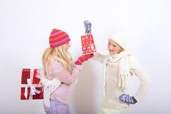 Femme de l'hiver de deux jeunes avec des cadeaux de Noël Photographie stock libre de droits