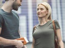 Femme de lancement parlant avec l'heureux homme dans l'aéroport photos libres de droits