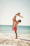 Femme de levage d'homme à la plage Image stock