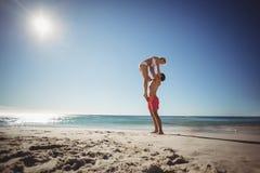 Femme de levage d'homme à la plage Images libres de droits