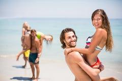 Femme de levage de jeune homme à la plage Photographie stock libre de droits
