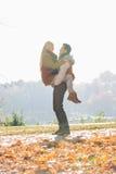 Femme de levage de jeune homme en parc pendant l'automne Photos libres de droits
