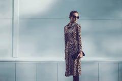 Femme de luxe de mode portant une robe de léopard avec la soirée d'embrayage de sac à main dans la ville image stock