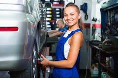 Femme de mécanicien travaillant aux machines de contrôle d'équilibre de roue Photographie stock libre de droits