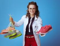 Femme de médecin donnant une paire d'espadrilles de forme physique image stock