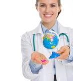 Femme de médecin retenant les pilules et le globe Photographie stock libre de droits