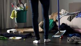 Femme de ménage choquée se tenant dans la chambre d'hôtel malpropre avec le balai et le seau de lavage image libre de droits