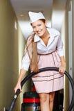 Femme de ménage heureuse avec l'aspirateur photos stock