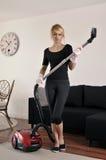Femme de ménage nettoyant à l'aspirateur dans la maison photographie stock