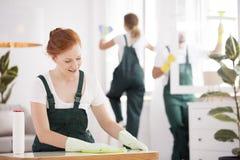 Femme de ménage de sourire essuyant la table Images libres de droits