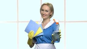 Femme de ménage tenant la bouteille et le chiffon de jet banque de vidéos