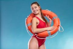 Femme de maître nageur en service avec la bouée de sauvetage de balise d'anneau Photo stock
